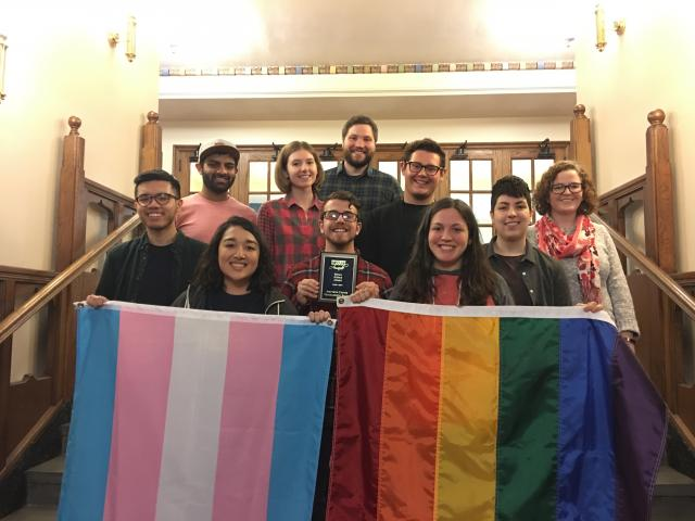 Ten past members of the Programming Board posing for a picture on a flight of stairs. In the front row there are students holding up a rainbow flag, a trans flag, and a Student Leadership Award in Social Justice.