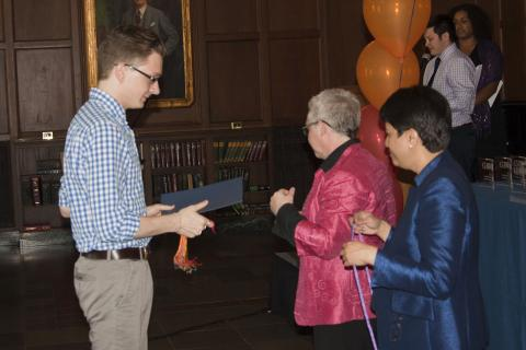 A student receives the Cornerstone Award at Lavender Graduation for his work on the Advocacy Board.