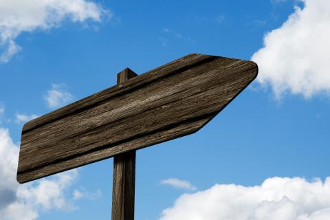 Photo of a wooden signpost pointing to the right against a clear blue sky.